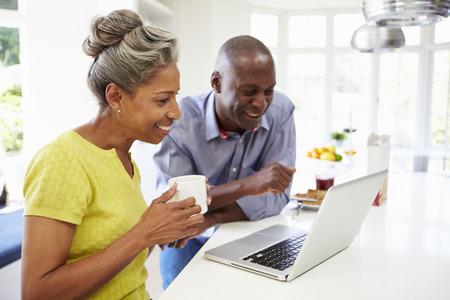 dos personas hablando: Pares del afroamericano maduro usando la computadora port�til en el desayuno