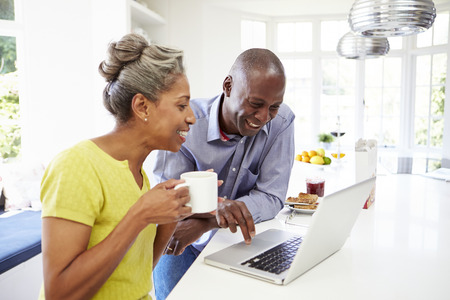 大人のアフリカ系アメリカ人カップルの朝食でラップトップを使用して 写真素材