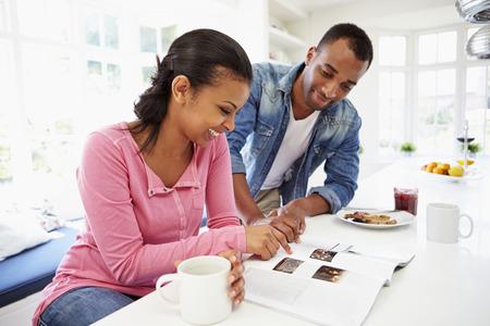 black couple: Couple Having Breakfast And Reading Magazine In Kitchen Stock Photo