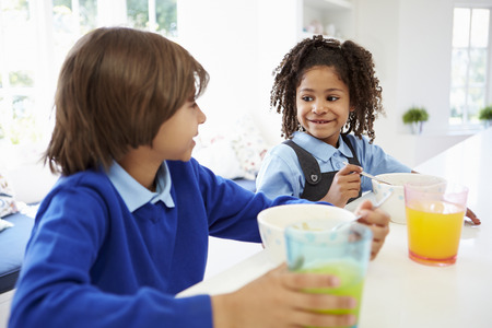 breakfast cereal: Two Children Having Breakfast Before School In Kitchen Stock Photo