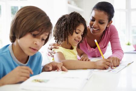 niños negros: Madre ayudar a los niños con la tarea en la cocina