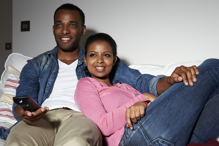 pareja viendo television: Pareja sentada en el sofá viendo la televisión juntos Foto de archivo