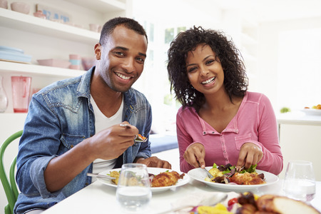 Young African American Couple Eating Meal At Home photo