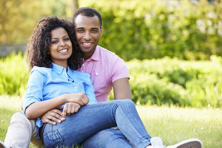 mixed race couple: Pareja joven rom�ntico sentado en el jard�n Foto de archivo
