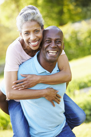 Mature Man Giving Woman Piggyback In Countryside Stock Photo