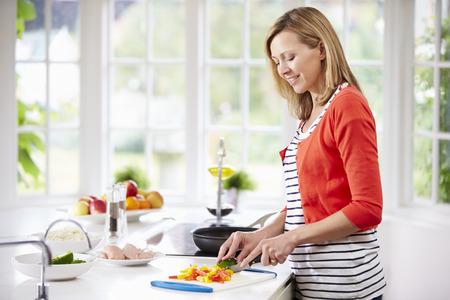 카운터에서 여자 서이 식사 할 수있는 부엌 준비 스톡 콘텐츠
