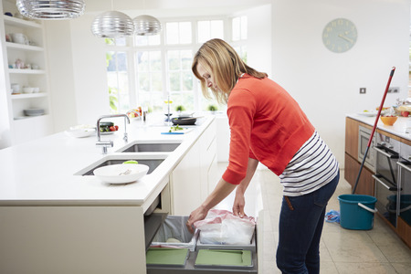 garbage bin: Woman Standing In Kitchen Emptying Waste Bin Stock Photo