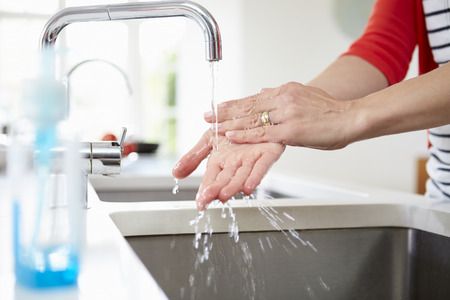 Close Up Van De Vrouw De Handen In Kitchen Sink