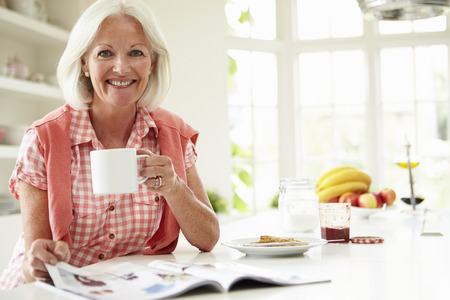 mature female: Middle Aged Woman Reading Magazine Over Breakfast Stock Photo