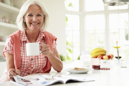 retrato de mujer: Mujer envejecida media de lectura Revista sobre el desayuno