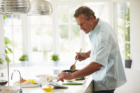 Middle Aged Man Following Recipe On Digital Tablet photo