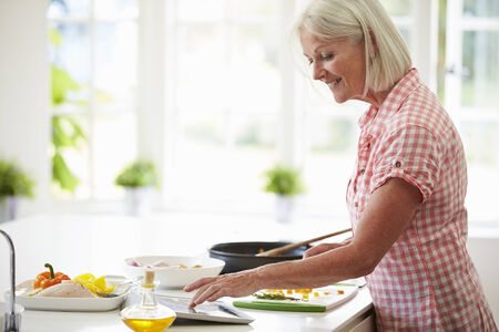 cutting vegetables: Middle Aged Woman Following Recipe On Digital Tablet