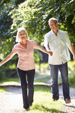 walking path: Romantic Middle Aged Couple Walking Along Countryside Path