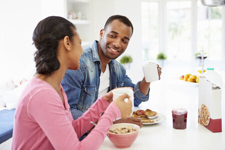 eating breakfast: Couple Having Breakfast In Kitchen Together