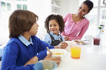 niños desayunando: Madre y niños que desayunan Antes de la escuela Foto de archivo