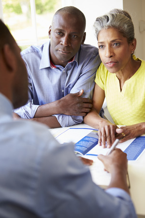 serious meeting: Mature Black Couple Meeting With Financial Advisor At Home