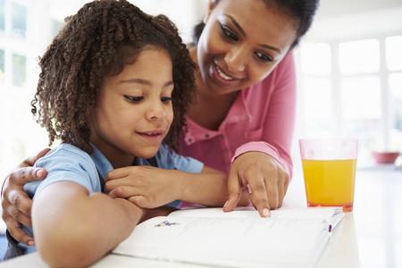 personas leyendo: Madre Hija de ayuda con la tarea en la cocina