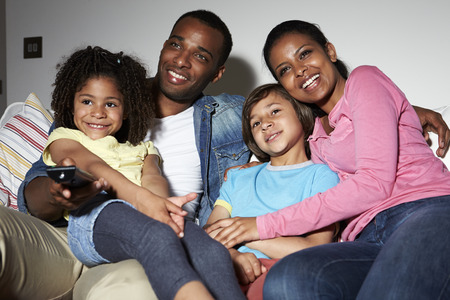 家族は一緒にテレビを見ながらソファに座って 写真素材