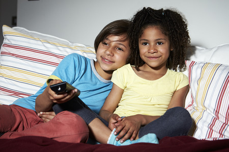 Two Children Sitting On Sofa Watching TV Together Stock fotó
