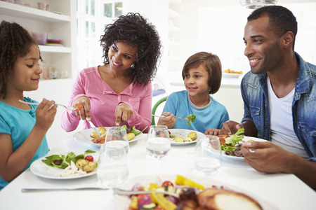 African American Family Eating Meal At Home Together