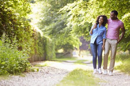 persona cammina: Giovani coppie dell'afroamericano che cammina nella campagna