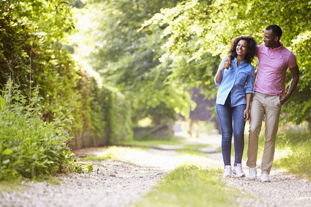 a couple: Young African American Couple Walking In Countryside