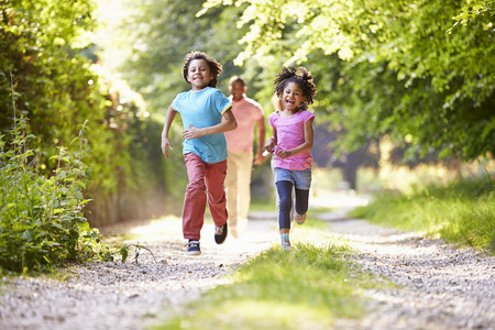 Children Running In Countryside With Father