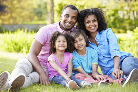 mixed family: African American Family Sitting In Garden Stock Photo