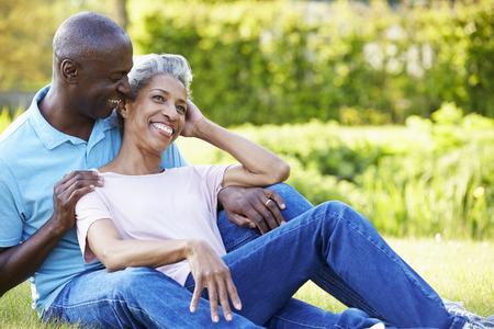 hombres maduros: Romántica pareja madura sentado en el jardín Foto de archivo