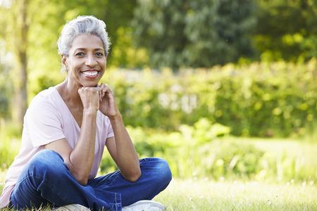 femmes souriantes: Attractive femme d'âge mûr assis dans le jardin Banque d'images
