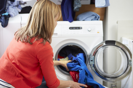laundry room: Woman Loading Clothes Into Washing Machine