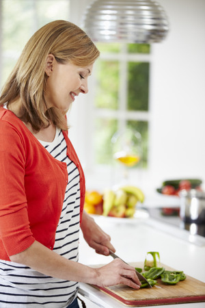 Woman Standing At Counter Preparing Meal In Kitchen Stock Photo