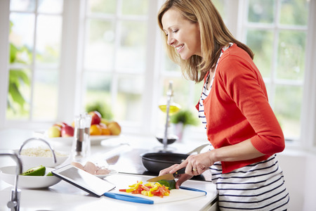Woman In Kitchen Following Recipe On Digital Tablet 스톡 콘텐츠
