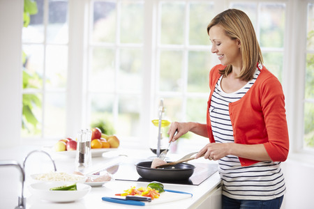 frying pan: Woman Standing At Hob Preparing Meal In Kitchen