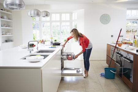 Vrouw borden in het afwasmachine Stockfoto