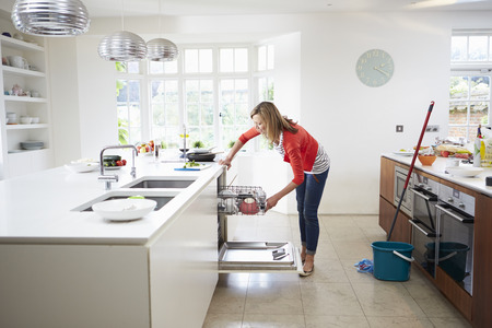 Woman Loading Plates Into Dishwasher Stock fotó - 31003901