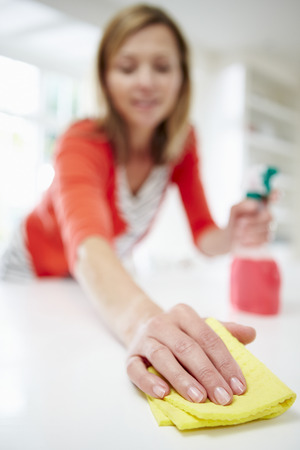 Woman Cleaning Surface In Kitchen