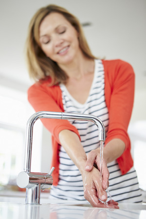 washing hands: Close Up Of Woman Washing Hands In Kitchen Sink