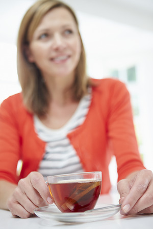 woman drinking tea: Woman Relaxing At Home With Hot Drink Stock Photo