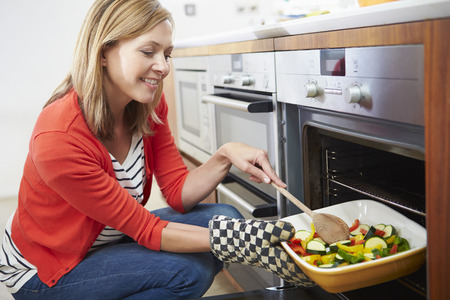 veggie tray: Woman Putting Tray Of Roast Vegetables Into Oven