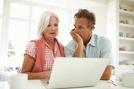 Bekommerd Midden-Ouder Paar Op Laptop Bekijkt Stockfoto
