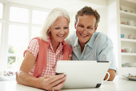 Smiling Middle Aged Couple Looking At Digital Tablet photo