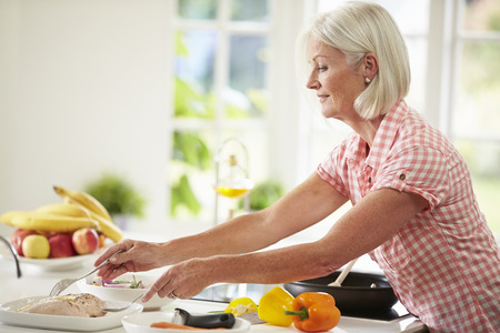 Middle Aged Woman Cooking Meal In Kitchen Archivio Fotografico