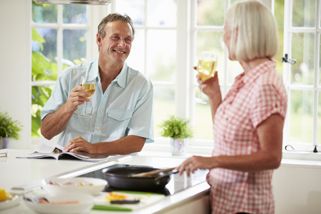Middle Aged Couple Cooking Meal In Kitchen Together photo