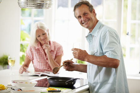 cutting vegetables: Middle Aged Couple Cooking Meal In Kitchen Together Stock Photo