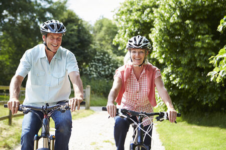 Middle Aged Couple Enjoying Country Cycle Ride Together photo