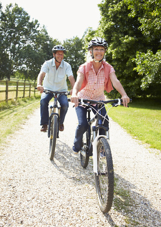 Middle Aged Couple Enjoying Country Cycle Ride Together Stock Photo