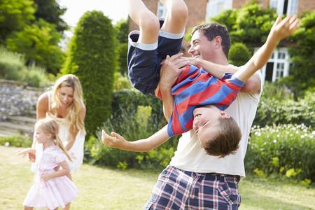 Familia que se divierte el jugar en Jardín