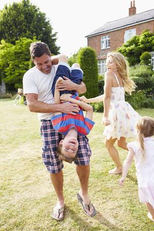 Vertical: Familia que se divierte el jugar en Jard�n Foto de archivo