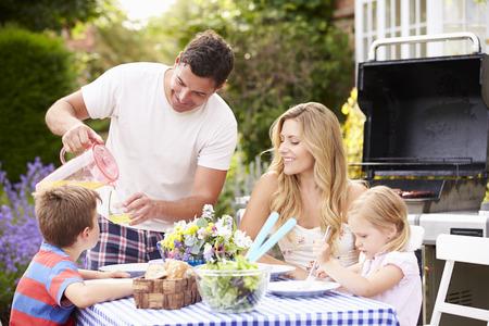 Family Enjoying Outdoor Barbeque In Garden photo